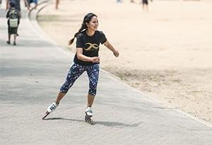 Vrouw inline-skaten op het strand